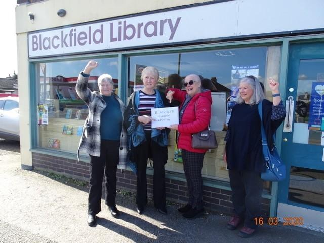Cllr Alexis McEvoy, second left, receives the petition from residents campaigning to save Blackfield library.