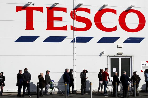 Daily Echo: People queue outside a Tesco Extra store in Madeley, Shropshire