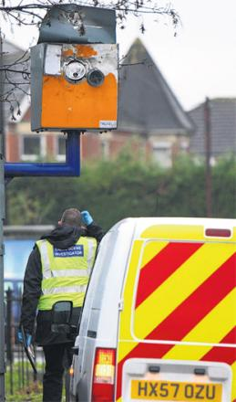 CAMERA PROBE: An investigation officer looks at the damaged speed camera in Bishopstoke.