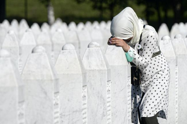 A woman by a grave stone in Potocari, near Srebrenica, Bosnia