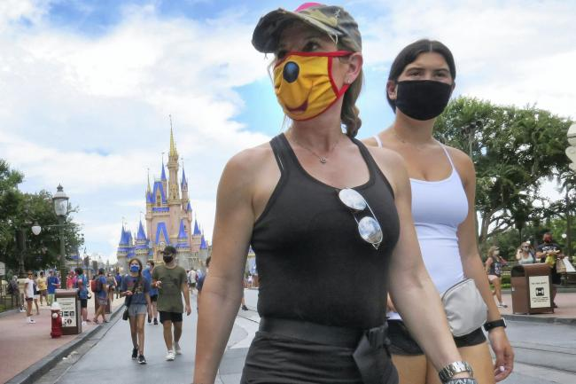 Guests wear masks as required to attend the official reopening day of the Magic Kingdom at Walt Disney World