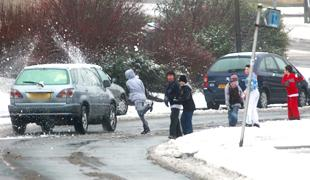 CLOSE RANGE: A gang of youths run into the road throwing snowballs at passing cars in Meggeson Avenue in Townhill Park.