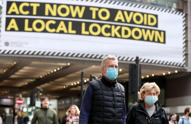 People wearing face masks walk past a advertisement on Market Street in Manchester, as the city is waiting to find out if the region will be placed into the Very High category with tier 3 lockdown restrictions to curb the spread of coronavirus. PA Photo.
