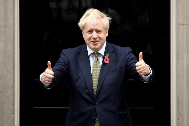 LONDON, ENGLAND - OCTOBER 23: UK Prime Minister Boris Johnson gives a thumbs up gesture as he poses with fundraisers for The Royal British Legion's Poppy Appeal outside Downing Street on October 23, 2020 in London, England. Due to the Covid-19 pandemi