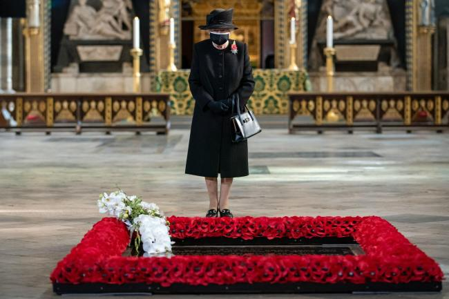 Queen Elizabeth II inspects a bouquet of flowers placed on grave of the Unknown Warrior Photo: Aaron Chown/PA Wire