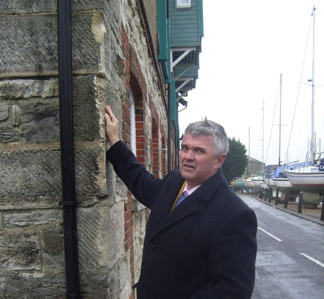 ACCIDENT SPOT: Councillor David Harrison examines the wall of the Heritage Centre.