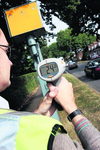 Daily Echo: Reporter Chris Walker with a speed gun alongside the speed camera box in Nuneham Courtenay yesterday