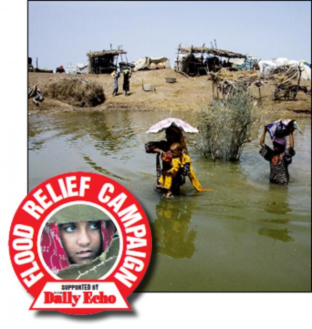 DISASTER: A family wade through floodwater in Bago Daro village, southern Pakistan.