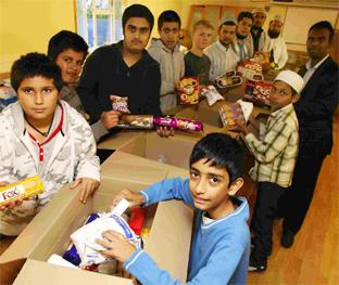 HELPING HANDS: Ten-year-old Afzal Sumro, 10, front, and colleagues pack boxes  destined for flood-hit Pakistan.           Daily Echo picture by Chris Moorehouse  Order no: 11079473
