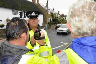 Daily Echo: PC Chris Forshaw helps instruct Chideock residents how to use a mobile speed camera