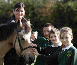 Fiona King introduces New Forest pony Knightwood Minx to children from Bassett Green Primary School, Southampton, l to r, Kacper Lewandowski, David McKenzie and Gosia Marczak, all 8