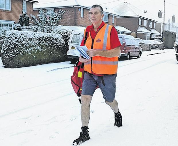Postman Dave Martin, age 60, battles through the snow in shorts and T-shirt to deliver his letters in Hamble.