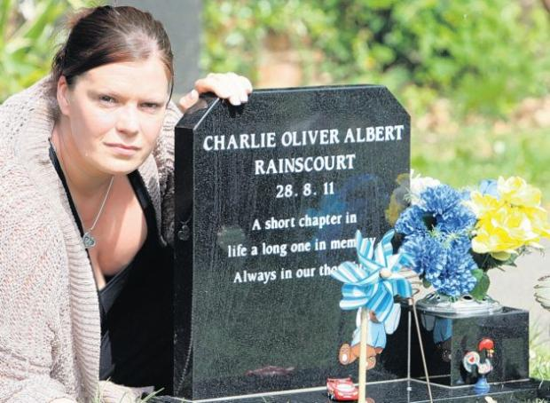 Kate Rainscourt at the grave of her baby son Charlie, from which thieves have stolen toys and flowers.