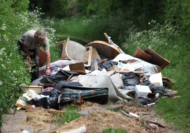 David Buckett looks at the pile of rubbish left by flytippers