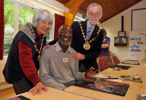 Basingstoke and Deane Mayor Cllr Martin Biermann and Mayoress Chansopha Biermann admire paintings by stroke survivor Angus Igwe