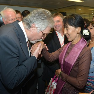 DJ Dave Lee Travis kisses the hand of Aung San Suu Kyi during her visit to the UK