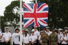Members of the armed forces raise the Union Flag at HMS Collingwood