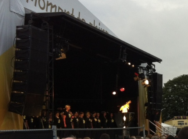 The cauldron burns the Olympic flame as the Rock Choir perfomr