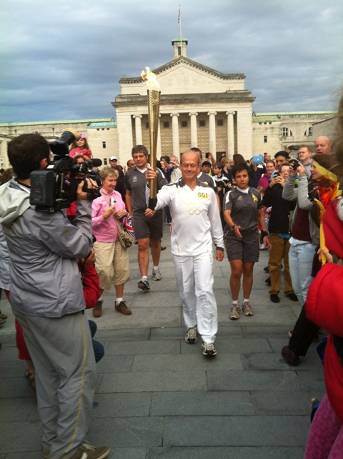 Early torch bearer makes his way through the crowd