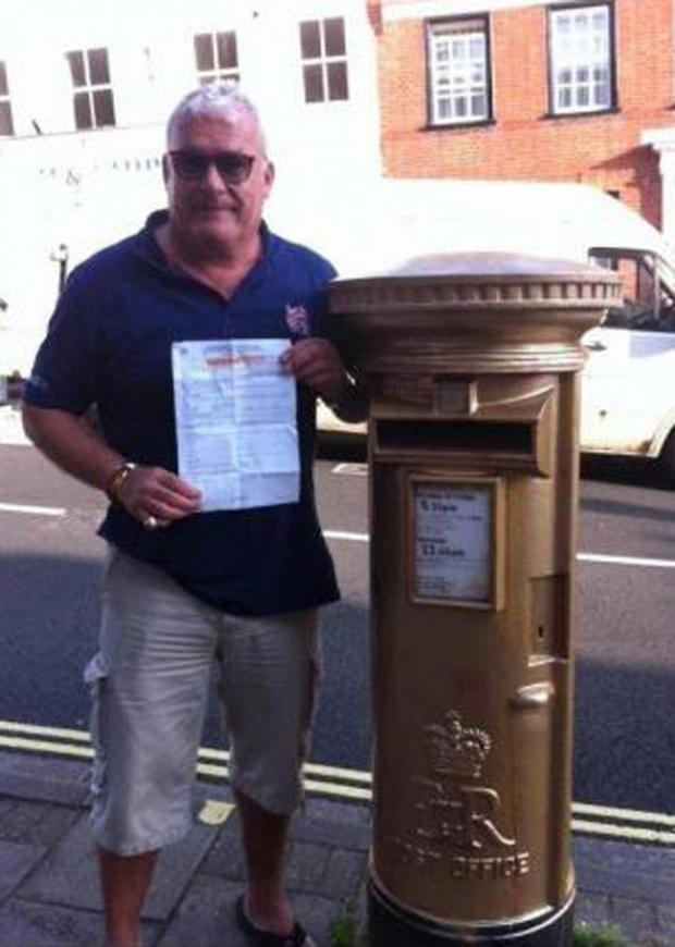 Rob Smith with his charge sheet by the Lymington postbox he painted gold in honour of sailor Ben Ainslie