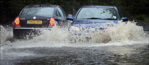 Cars negotiate the flooded road at Stoneham Lane, Eastleigh, last month, following heavy rain.
