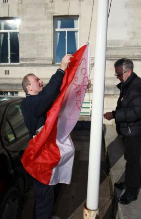 Mike King raises the Socialist Party flag at the Civic Centre.