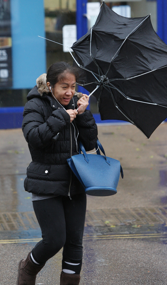 A woman battles against the wind and rain in Totton