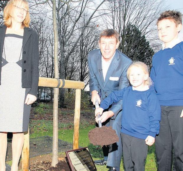 NEW LIFE: The youngest and oldest pupils, Alana Bailey, four, and Shane Johnson, 11, help Mike Osman and head teacher Lucy Jones plant a tree