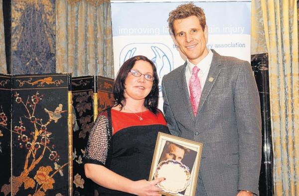 Christina Corp receives her award from double Olympic gold medallist and Headway vice-president James Cracknell.