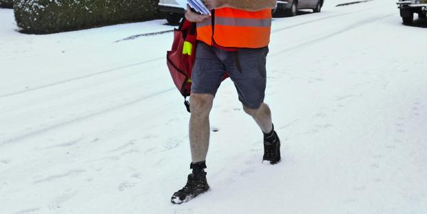 Stock image of a postman battling through snow earlier this year