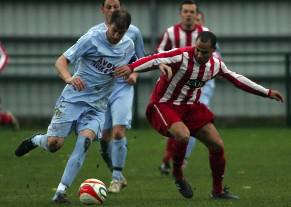 Sholing FC (red and white stripes) in action against Mangotsfield United at VT Sports Ground
