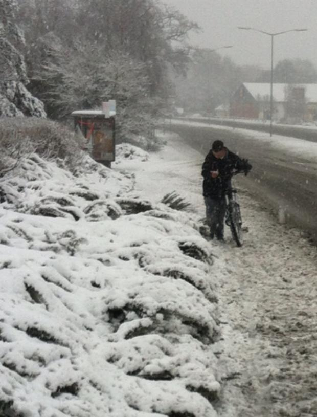 A man pushing his bike through snow in Ringwood.