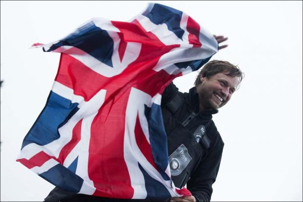 Alex Thomson celebrates his podium finish in the Vendee Globe race