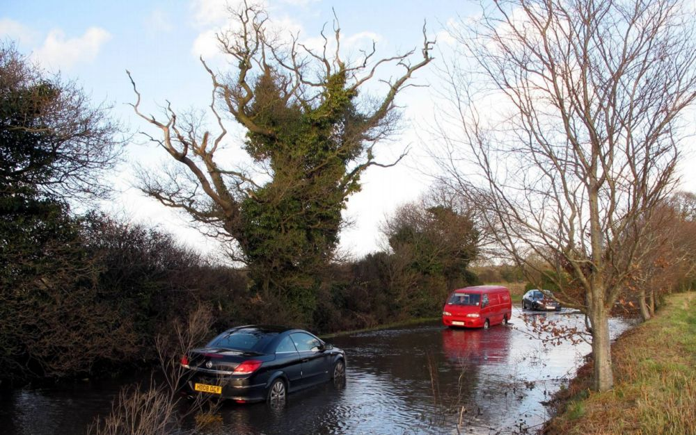 This motorist was marooned after driving through a 'road closed' sign at Derritt Lane near Bransgore yesterday.