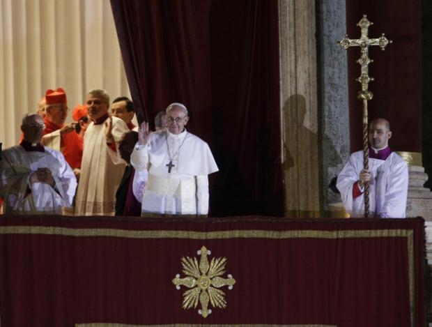 Pope Francis flanked by Monsignor Guido Marini, master of liturgical ceremonies, waves to the crowd from the central balcony of St. Peter's Basilica at the Vatican,