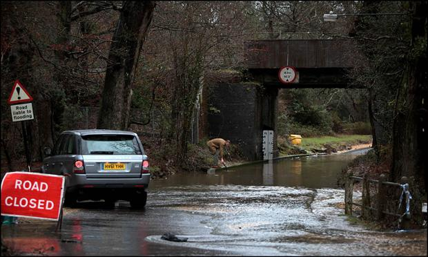 A driver checks the depth of the water on Balmer Lawn Road before turning back.