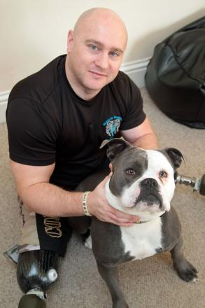 Soldier Jim Wilson, who lost both his legs in Afghanistan in 2011, with his dog Vallon.