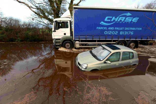 A truck passes a car abandoned in the flood near Bransgore.