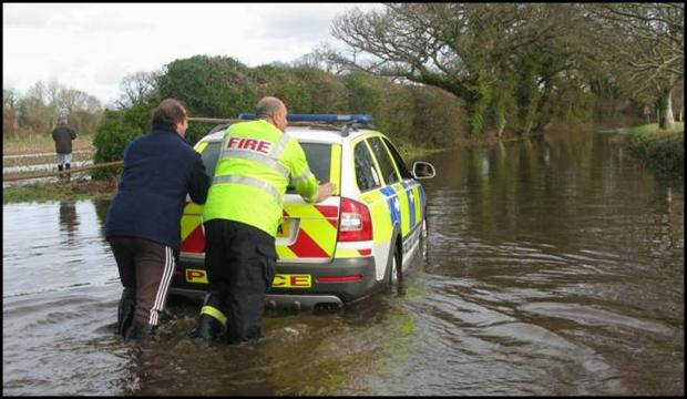 police officer rescued - after driving through flood