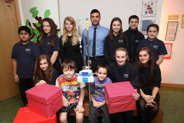 Pupils from Cantell School present gifts to children at Southampton General Hospital. Here, patients Max Tucker and Reggie Miller are pictured with the pupils.