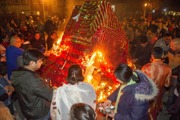 Worshippers gather around a huge bonfire at the Vedic Hindi Society Temple