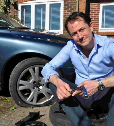 CAR MISERY: TV reporter Richard Gaisford with his damaged tyre.