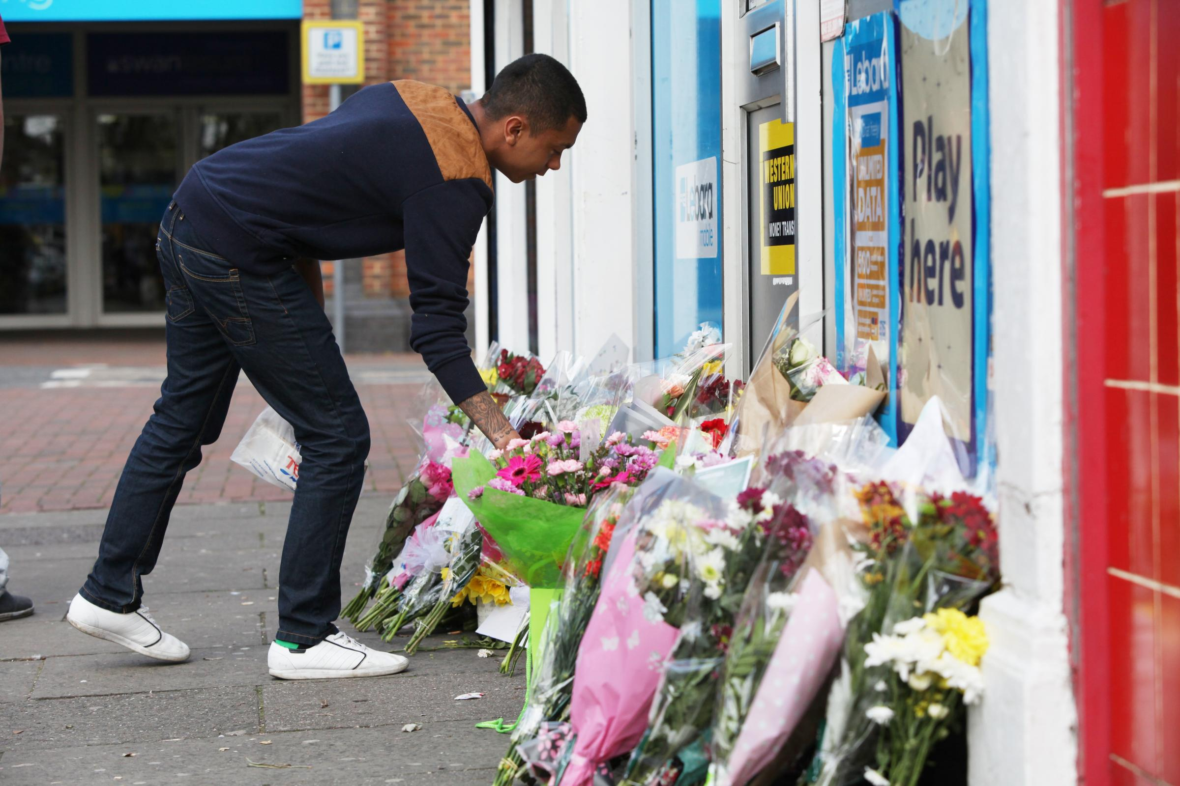 Flowers are laid at the scene of the murder