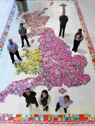 DIRECTIONS: Ordnance Survey staff at Adanac Park with a giant map of Great Britain made of old maps that have been handed in by the public in exchange for new one