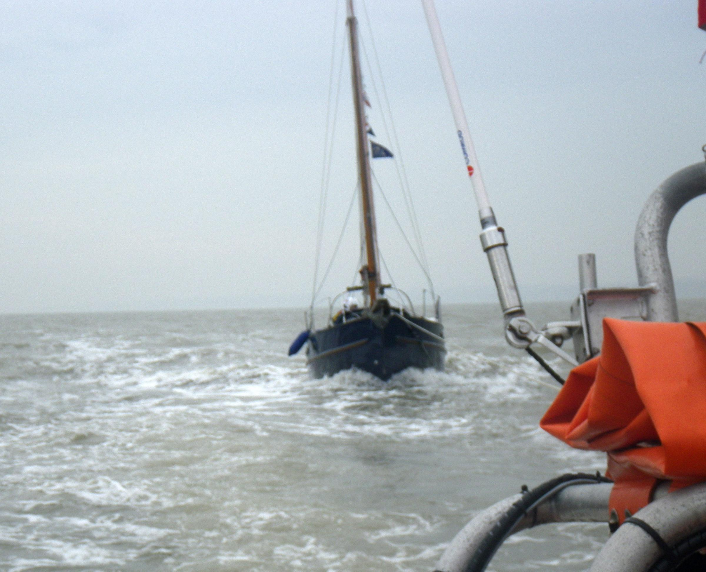 The 23-ft yacht is towed into Cowes by Solent Coastguards