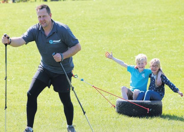 John pulls along his children as part of his training