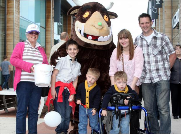 Four-year old twins Reuben and Zachery (in walking frame) Smith with brother Harry, 10, mum Haanagh, dad Mike, fundraiser Glenys Kirkpatrick and the Gruffalo.