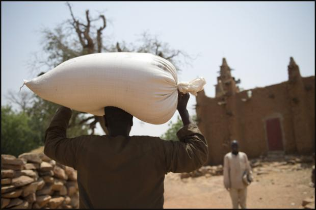 A man in Songho receives a sack of millet thanks to the efforts of Christian Aid's part