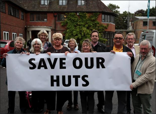 Milford beach hut owners make their point outside the council offices.
