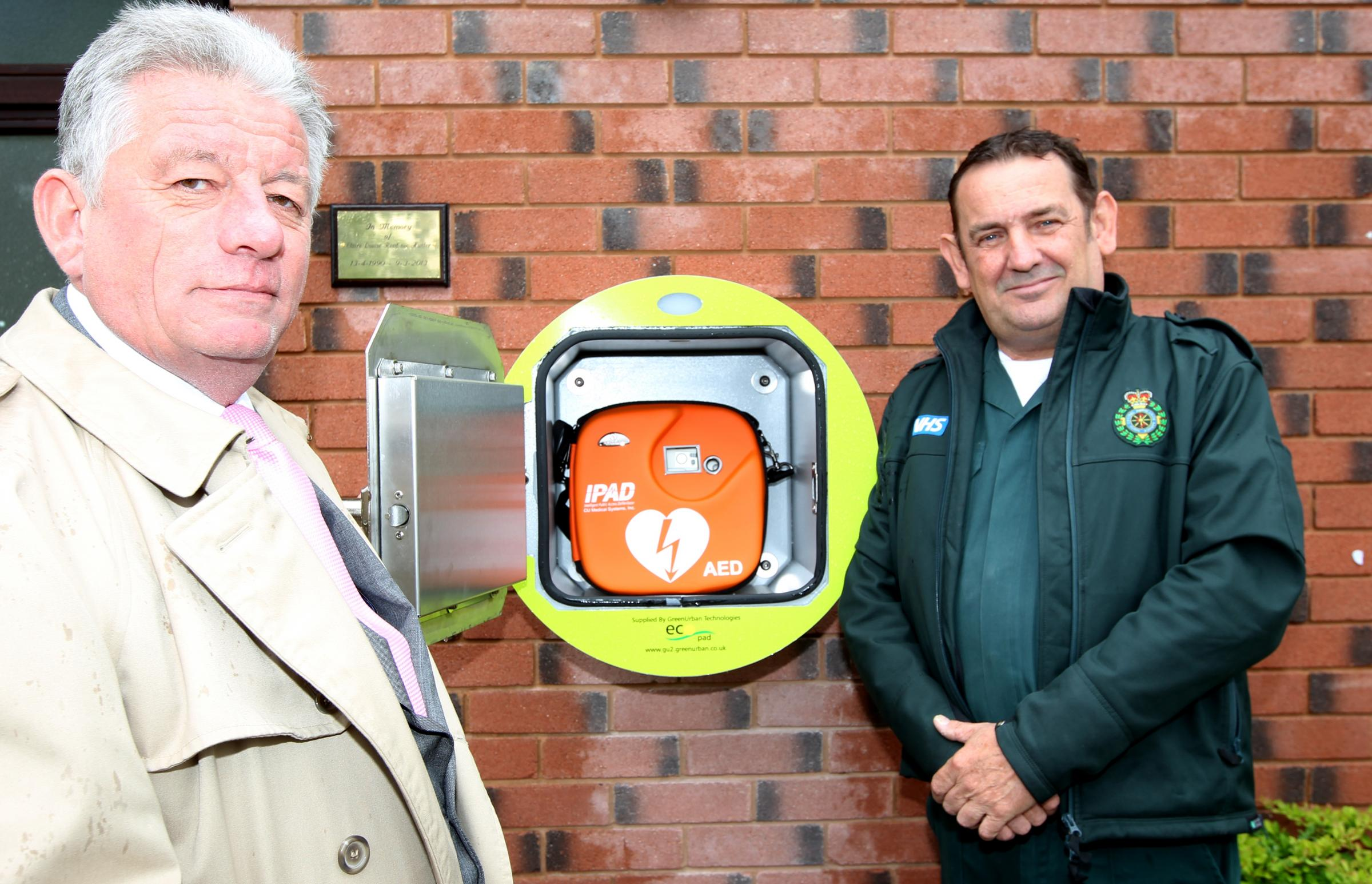 Graham Hunter, left, unveils the defibrillator with South Central Ambulance Service's Peter Hackett